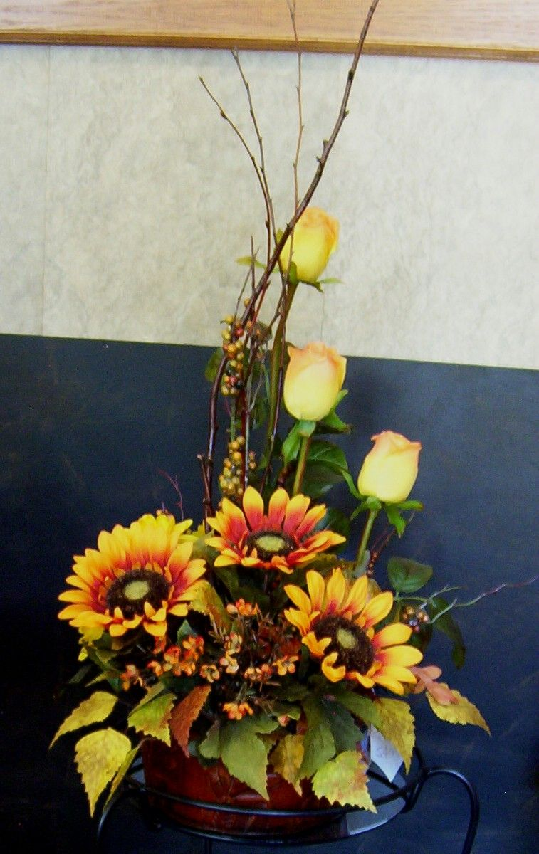 A tall arrangement for a country home made with artificial orange/gold sunflowers, yellow mums, orange rosebuds , twigs and berry stems. http://www.dectouch.com