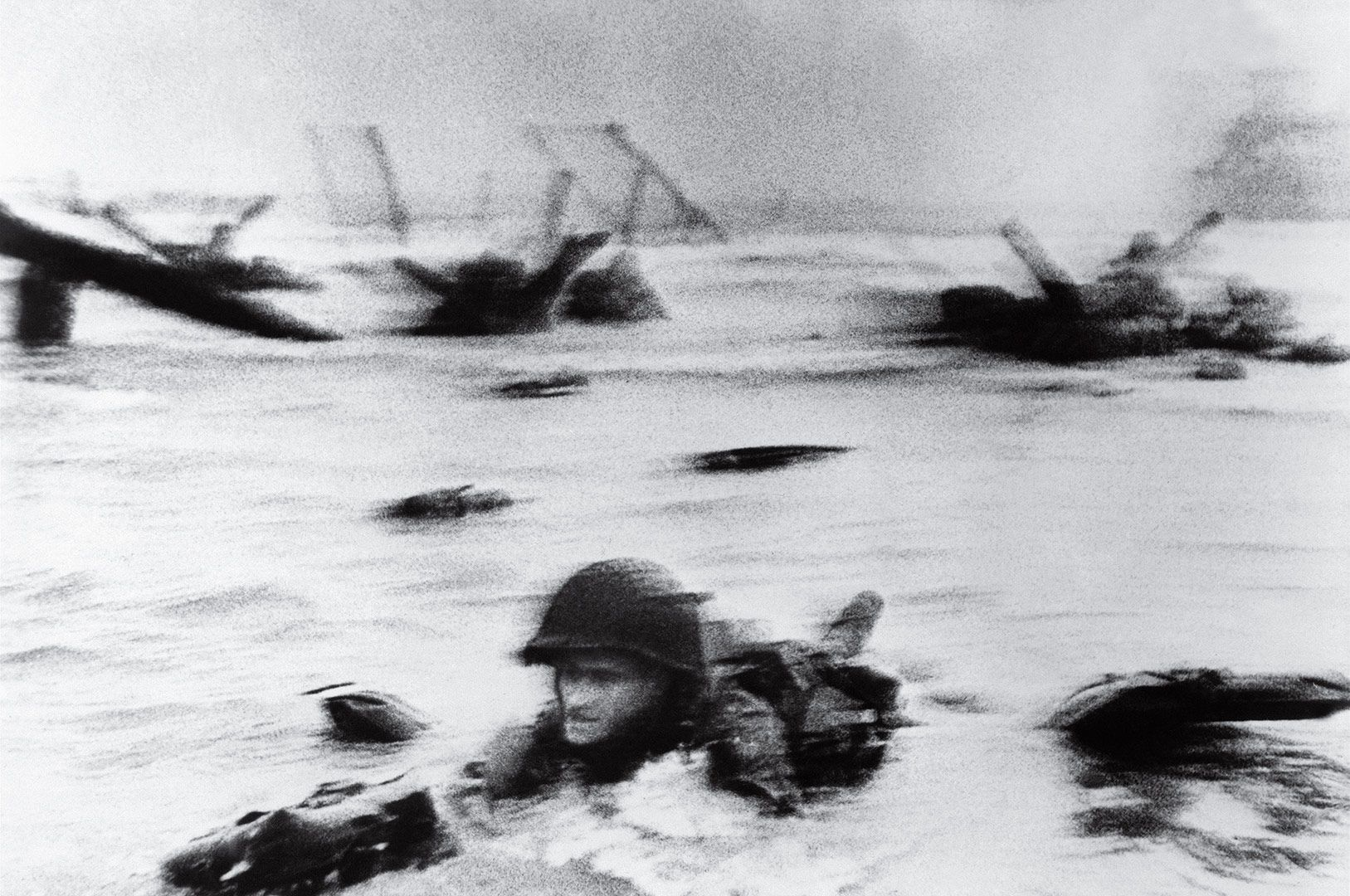 """ROBERT CAPA / D-Day, 1944 / """"It never occurred to me until later that in order to take that picture, Capa had to get ahead of that soldier and turn his back on the action."""""""