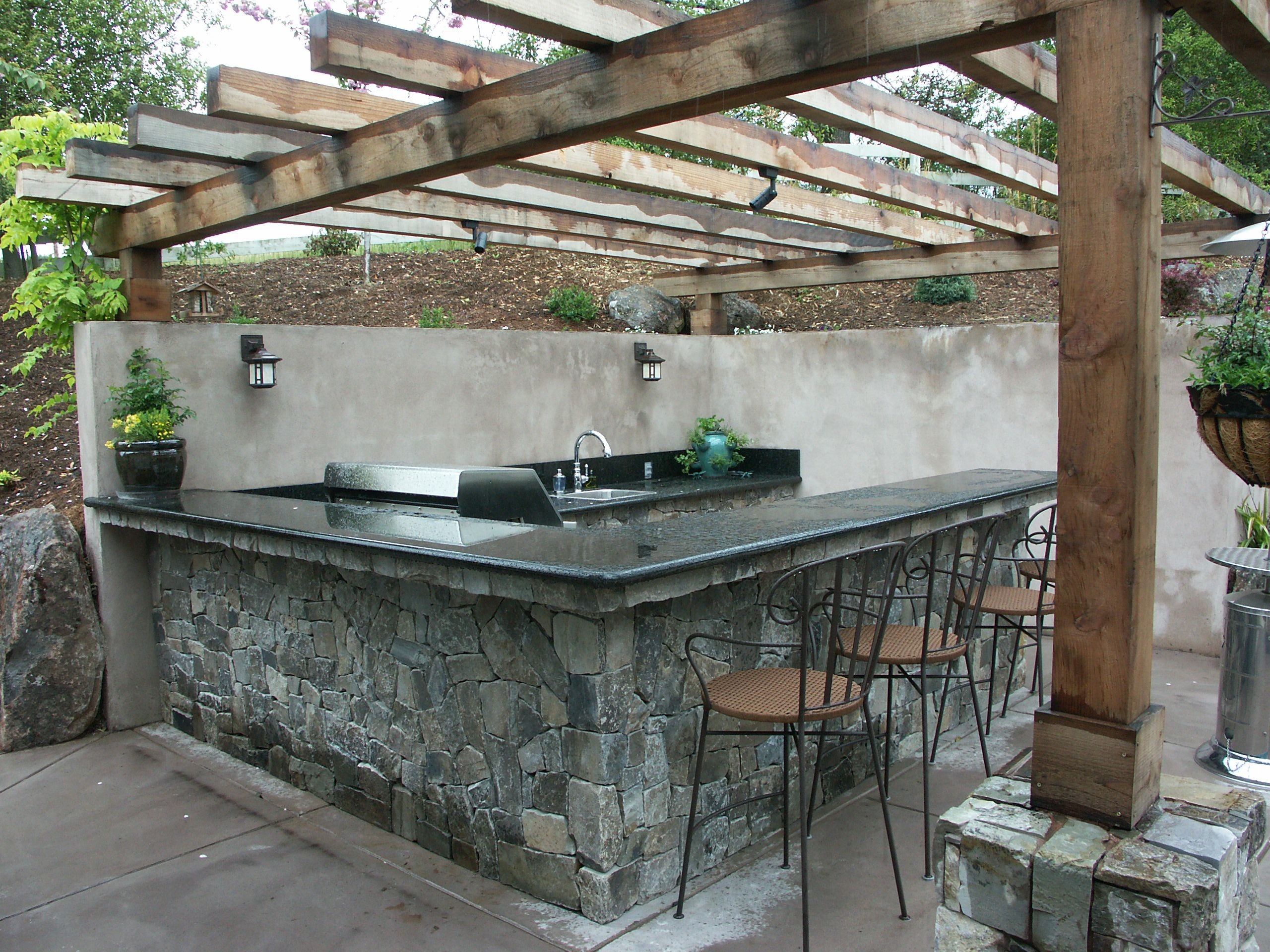 outdoor kitchen cut into slope. stone veneer finish with granite