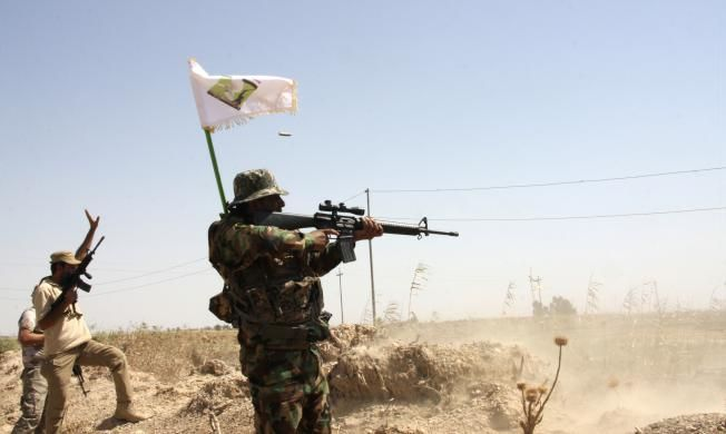 Members of the Mehdi Army, loyal to radical cleric Muqtada al-Sadr, clash with Islamic State militants outside the city of Tikrit September 8, 2014. Picture taken September 8, 2014. REUTERS/Stringer