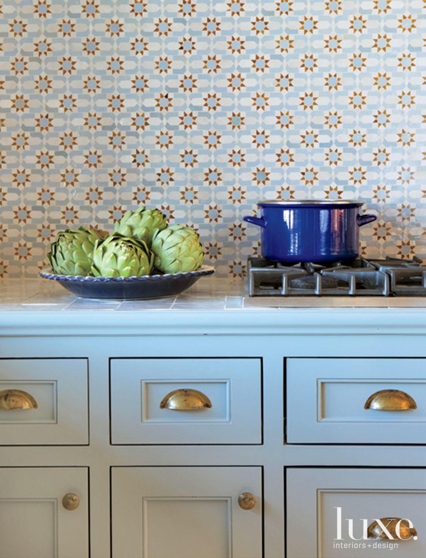 Pretty tile backsplash and blue cupboards