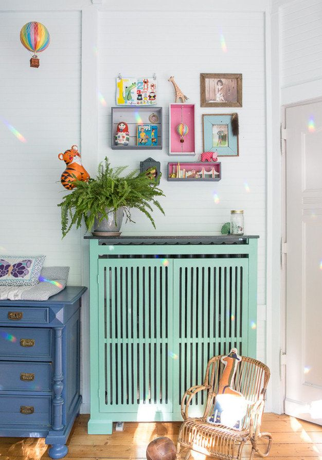 Bright, tropical colour palette in kids room with mint green and blue storage, wall mounted crates and white walls.