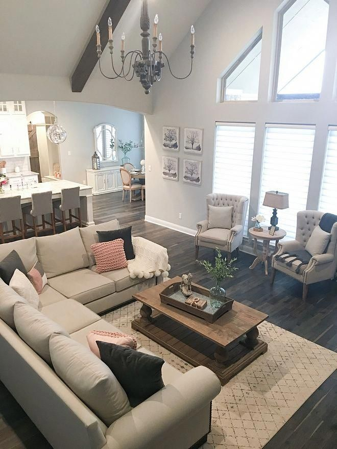 Farmhouse Living Room Vaulted Ceiling with Beams and French Chandelier Paint Color Sherwin Williams Repose Gray SW 7015 Wall Color Sources on Home Bunch #Farmhouselivingroom #Farmhouse #livingroom #vaultedceiling #beamceiling #beamvaultedceiling #vaultedceilingdecor