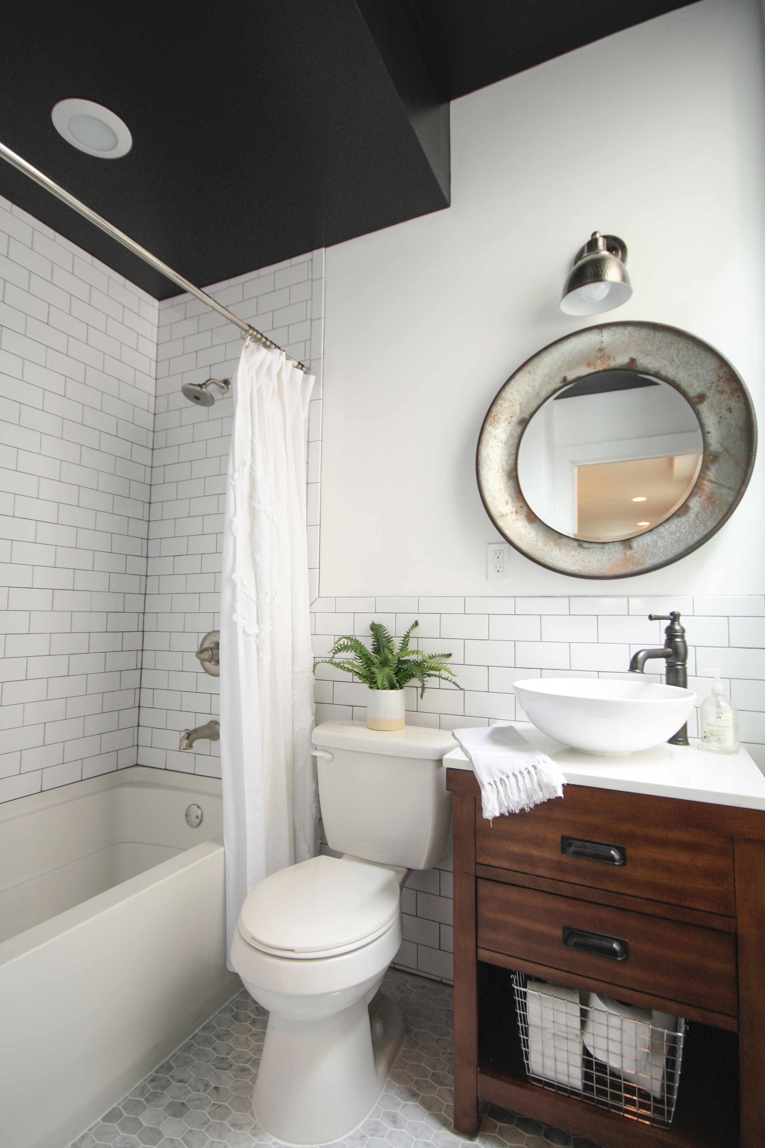 Industrial Schoolhouse style bathroom with Black ceiling with white subway tile and dark grout