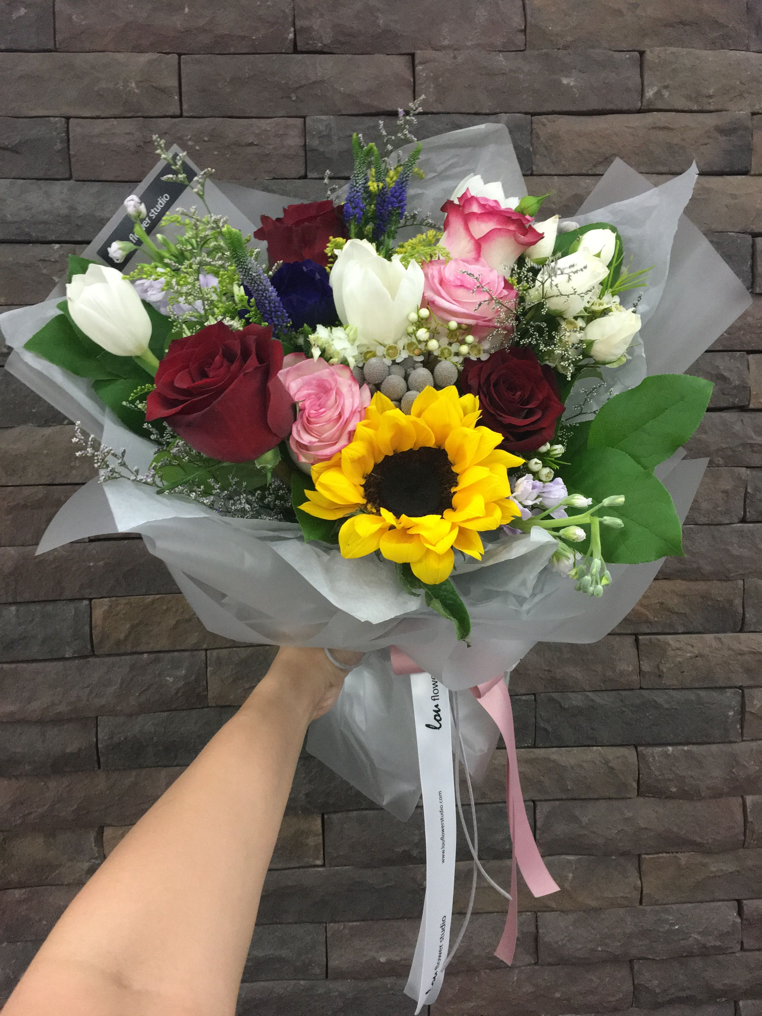 A Happy Garden Themed Bouquet With Sunflower Tulips And Roses Bouquet Sunflower Arrangements Garden Pictures