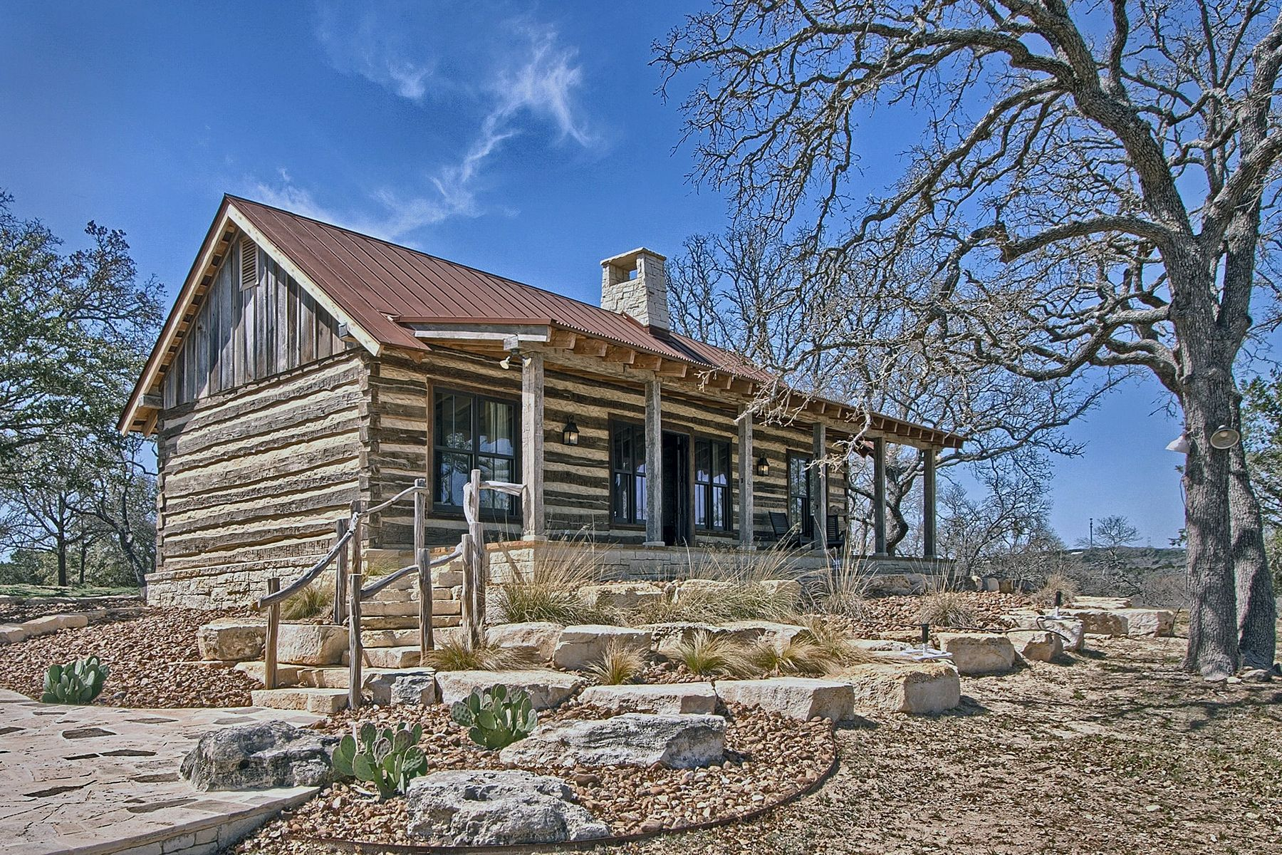 Log cabin in the texas hill country landscape for Cabin builder texas