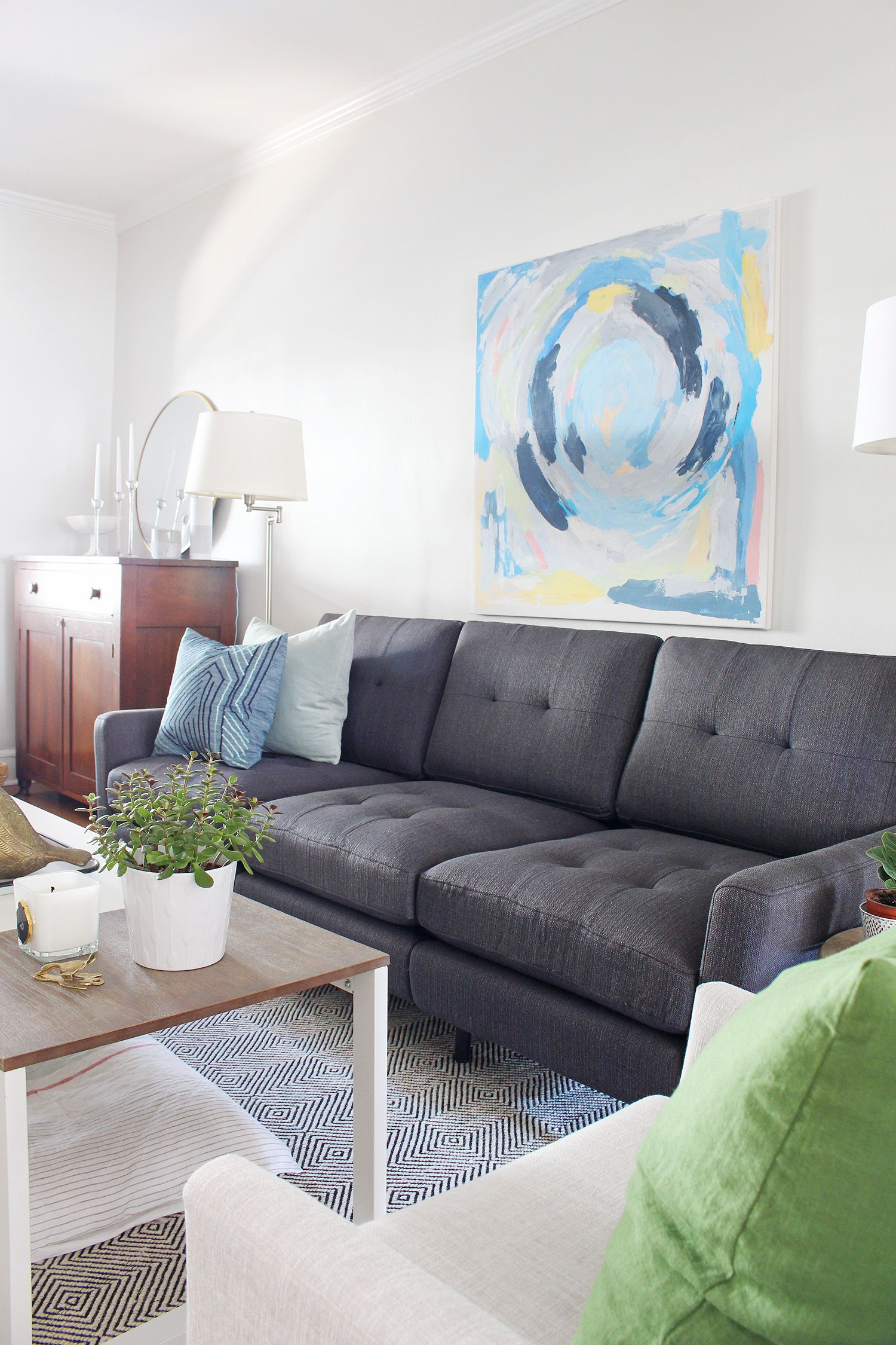 A mid century modern eclectic living room mixes new and old to create a cozy space the neutral charcoal gray sofa has pops of color thanks to the blue