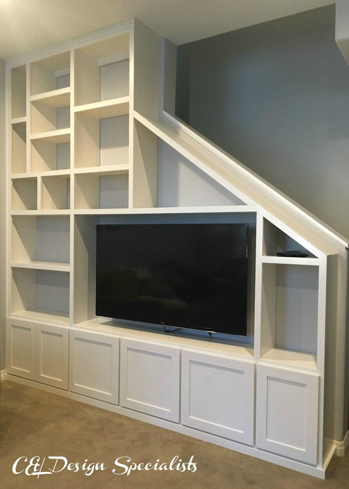 Entertainment center designed to fit staircase wall