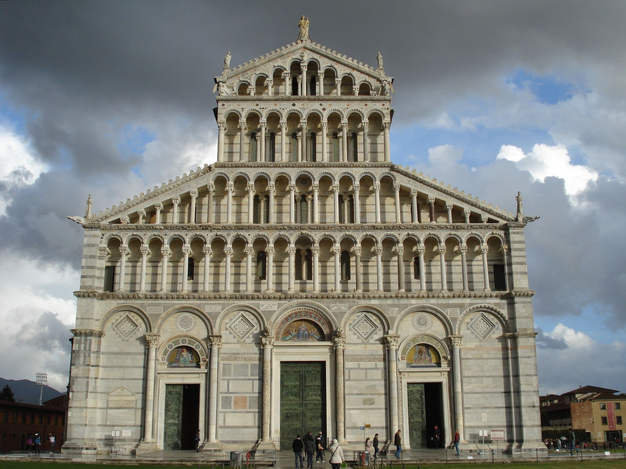 ROMANESQUE ARCHITECTURE, Italy - Facade of the cathedral of Pisa, begun 1063. The cathedral (Duomo) of Pisa was founded in 1063 after the victory of the Pisan fleet over the Saracens near Palermo. Stylistically it was a variation of the Mediterranean basilica plan with influence from Near Eastern architecture. The building has also Lombard overtones, especially in the facade with its four registers of freestanding gallery work.