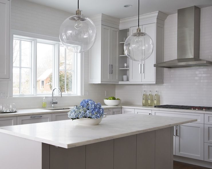 Gorgeous Kitchen Features A Pair Of Clear Glass Globe Pendants Hanging Over  A Center Island Painted