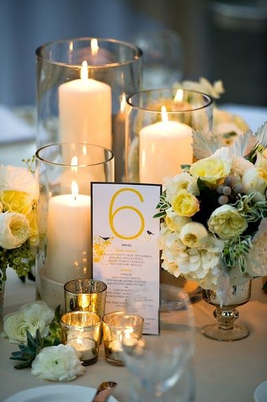 Yellow wedding idea. candle on glasses and bunch of white and yellow flowers.