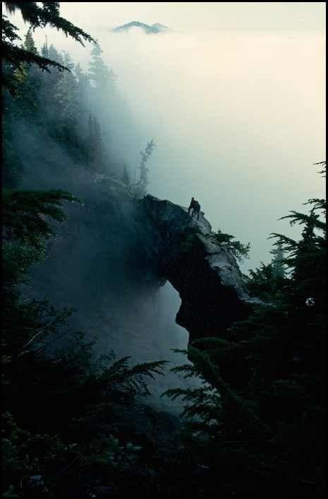 Washington 1963. Escalador parado junto a la cima de un puente natural de roca en Mt. Rainier.