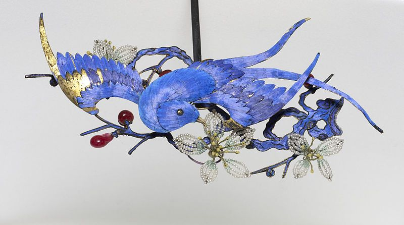 This pair of ornaments (with Walters 86.14) and headdress (Walters 86.3) were likely once worn by the empress dowager, the effective ruler of China during the later years of the Qing Dynasty. It is an exquisite example of Chinese decoration and the symbolism used to express one's rank. The small phoenixes emerging from the surface represent the empress, while the myriad of pearls and gemstones mark this piece as something special for the adornment of the highest ranking woman in Chinese…