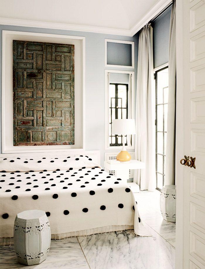 Polka dot bedding in white bedroom with carved artwork