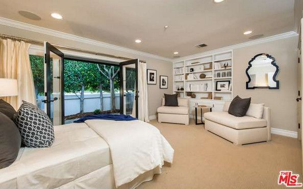 The Guest Bedroom - A guest bedroom features a built-in bookshelf, wall-to-wall carpeting, and contrasting crown molding. Mila Kunis' Los Angeles Mansion