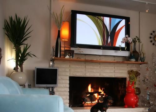 fireplace w tv above and simple wooden shelf clean design