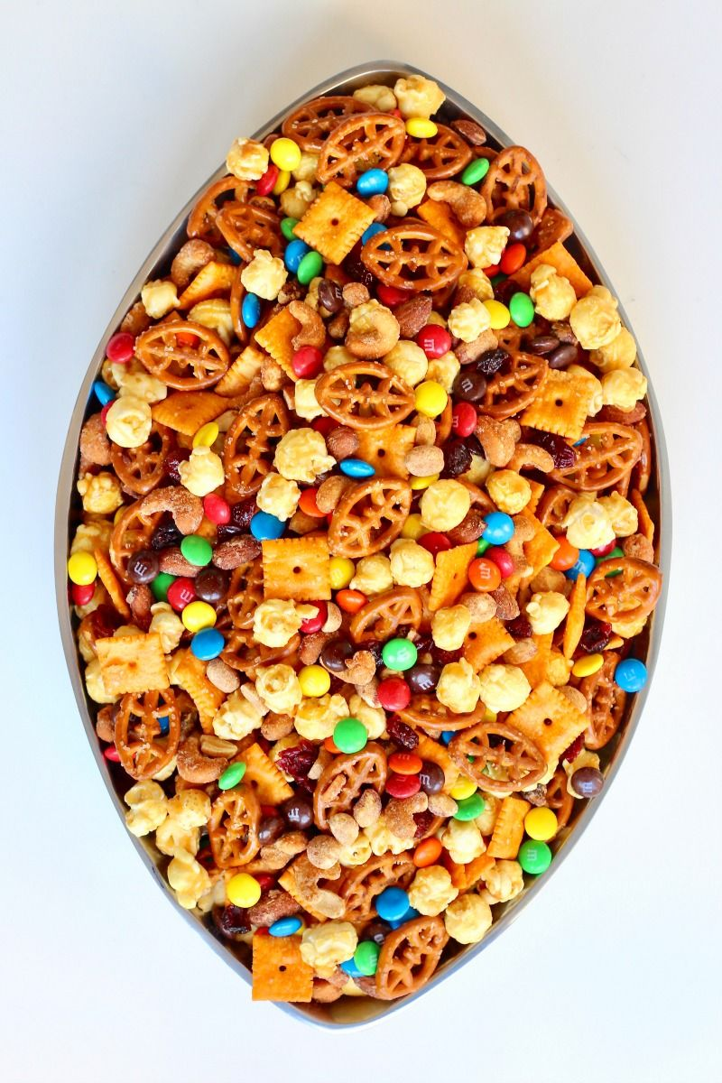 Win big at your next tailgate or watch party with this tasty snack mix filled with sweet and salty goodies including the cutest football shaped pretzels! It's the most wonderful time of the year! It's football season, y'all! Woohoo! It's no secret we're big fans of football in my family and when it comes to... #footballpartyfood
