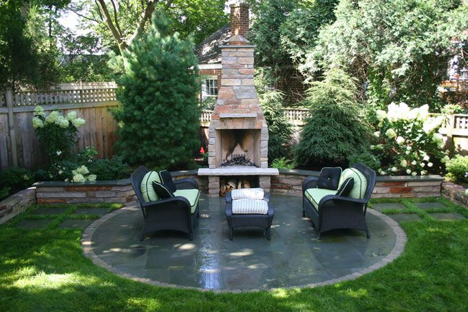 cozy outdoor stone fireplace with wood storage beneath heffernan