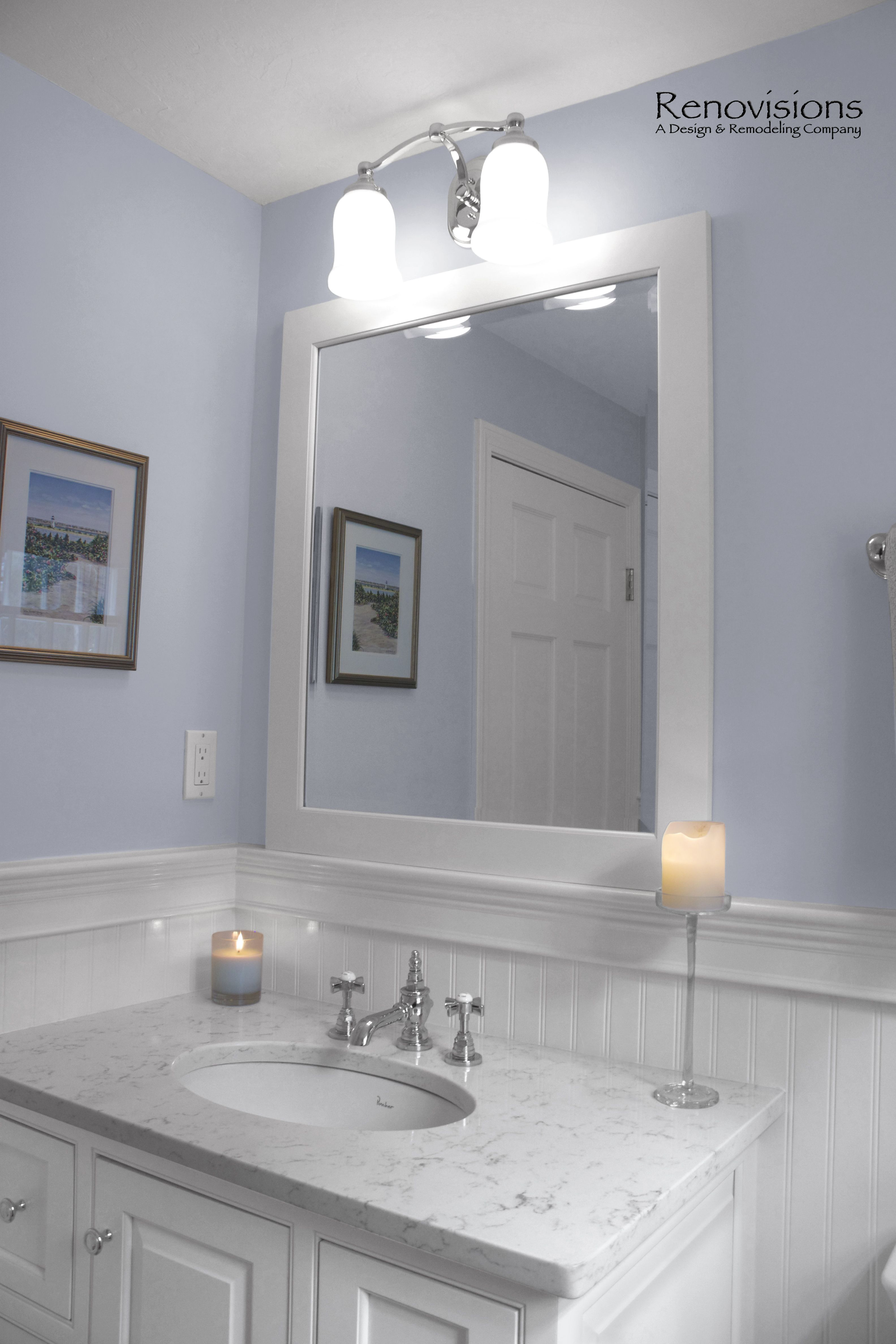 Half Bath Remodel by Renovisions Furniture like inset wood vanity in white painted finish with matching framed mirror Carrera look quartz countertop and