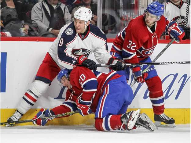 Montreal Canadiens Christian Thomas is held down by Columbus Blue Jackets  Gregory Campbell while Habs Brian Flynn watches during first period of National Hockey League game in Montreal Tuesday December 1, 2015.