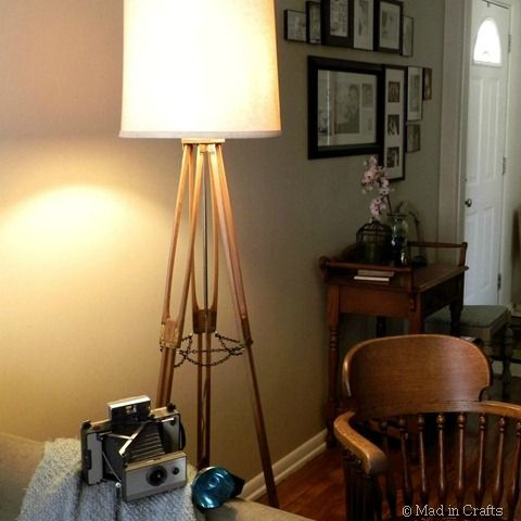 Vintage camera tripod repurposed into a floor lamp. Great idea for industrial decor or a photograph-themed room.