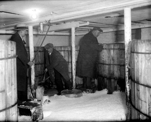 Prohibition agents, trying to keep dry during a raid, seek higher ground as a sea of foamy beer floods the floor of an illegal brewery located at 3316 East Willis on Detroit's East Side. (3-7-1932)