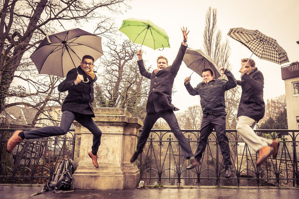 men group picture jumping in rain