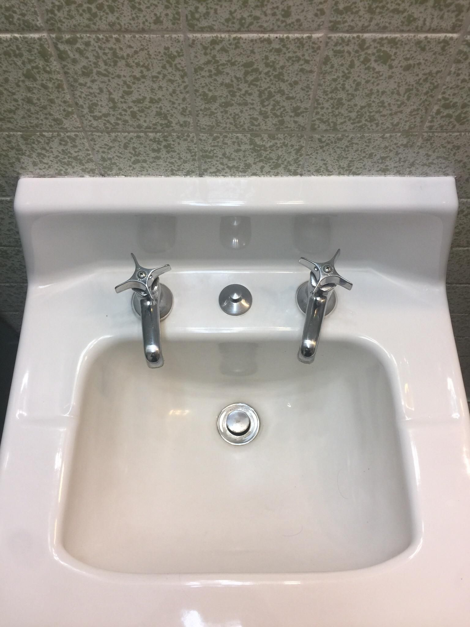 This bathroom sink has separate faucets for hot and cold water ...