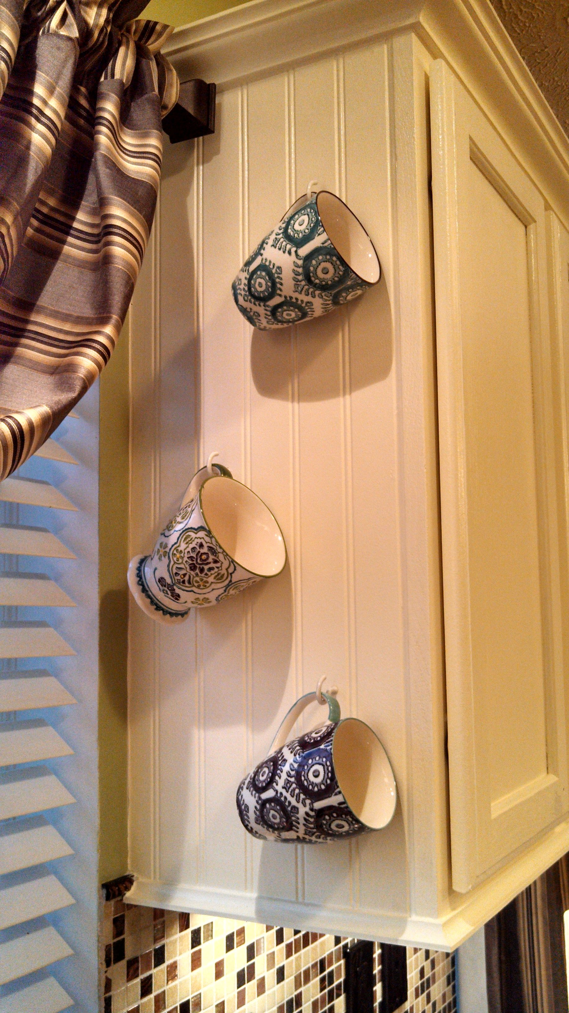 Decorative coffee mugs dress up the sides of kitchen cabinets and ...