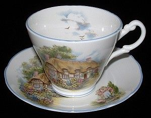 This is a bone china cup and saucer featuring the famous thatched cottage of Anne Hathaway, the love of William Shakespeare, in Stratford on Avon, England. The teacup and saucer was made by Allyn Nelson, England for Royal Patrician in the 1990s.