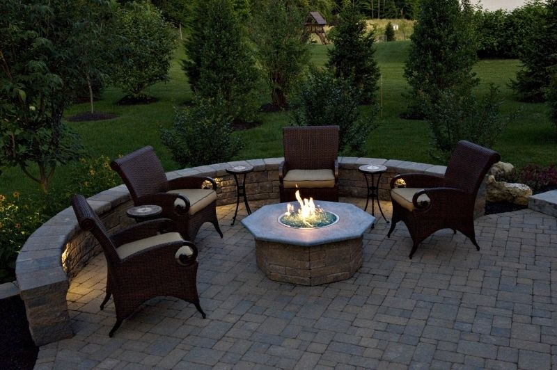 a custom patio with sitting walls and a fire pit containing fire