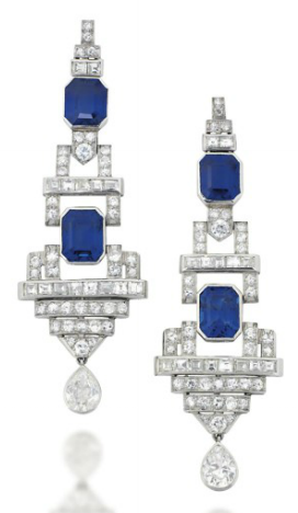 A PAIR OF ART DECO SAPPHIRE AND DIAMOND EAR PENDANTS. Each tapering geometric panel, set with two rectangular cut-cornered sapphire accents, among a single and square-cut diamond articulated surround, suspending a single pear shaped diamond drop, 6.5cm long, post fittings. #ArtDeco #earrings