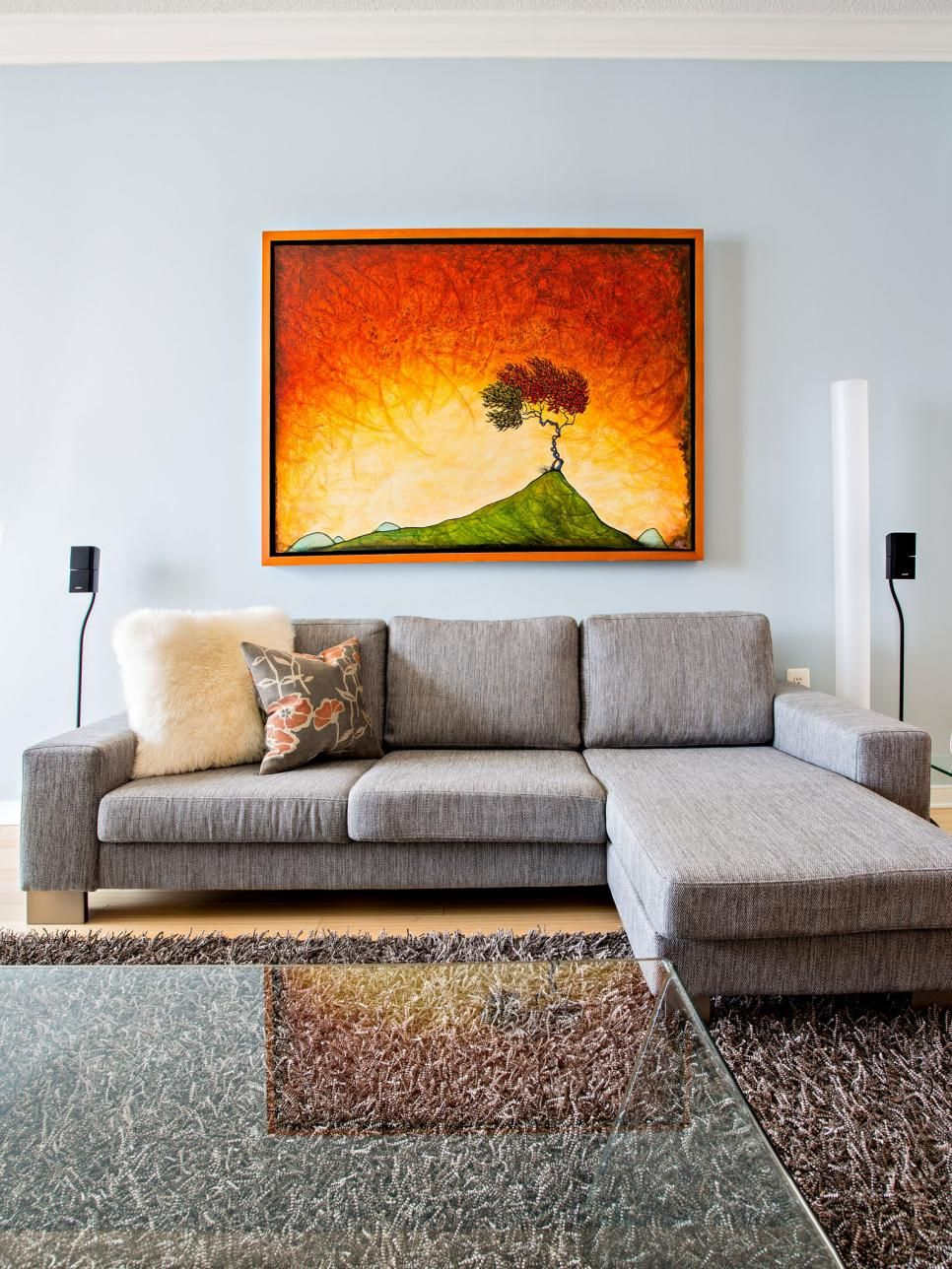 Bold orange-dominated artwork makes a strong focal point in this pale blue living room. A shaggy brown rug and light gray sectional sofa with a chaise round out the room's color palette.