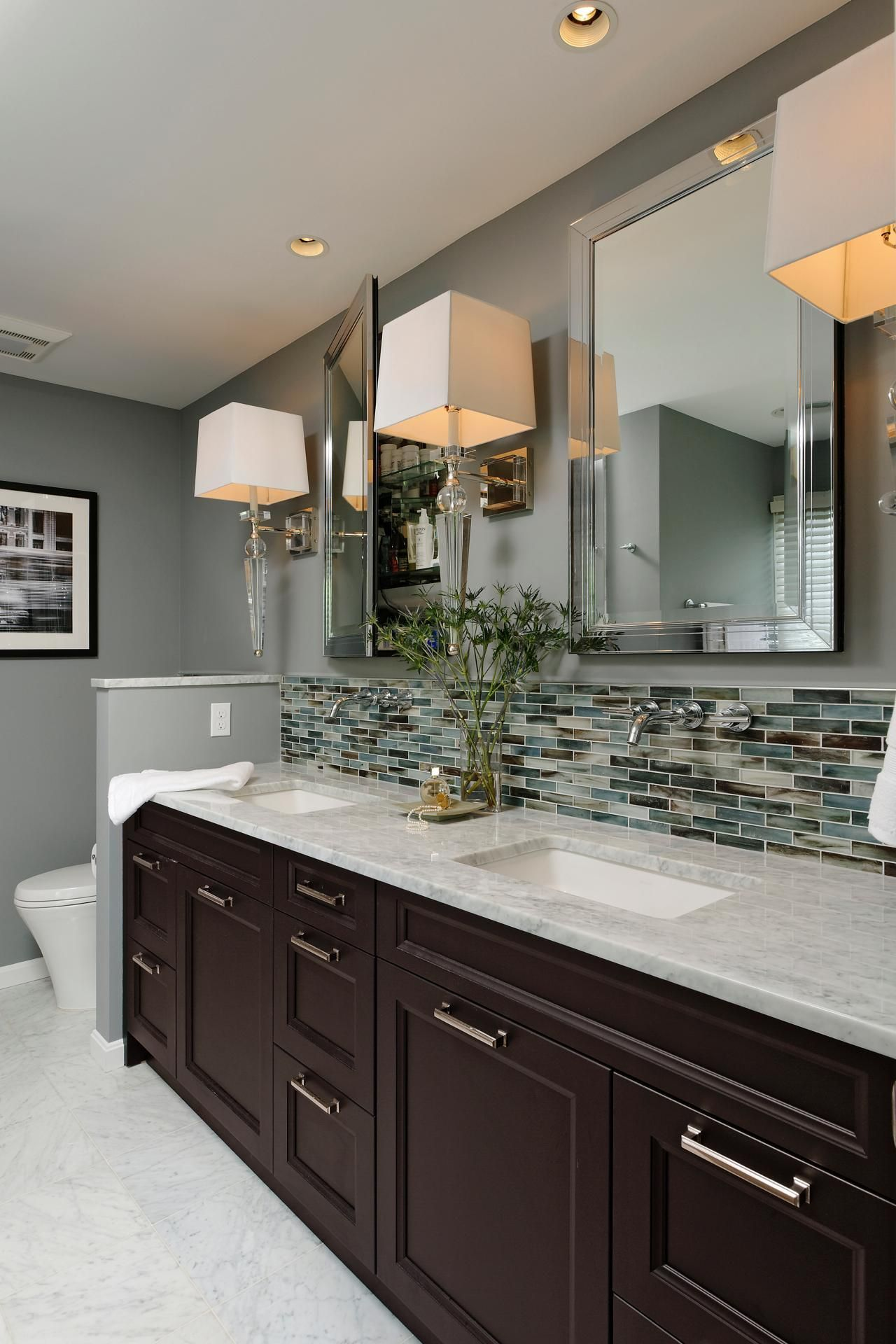 This gray contemporary bathroom features a double vanity design with a Carrera marble countertop glass tile backsplash and polished chrome sconces and