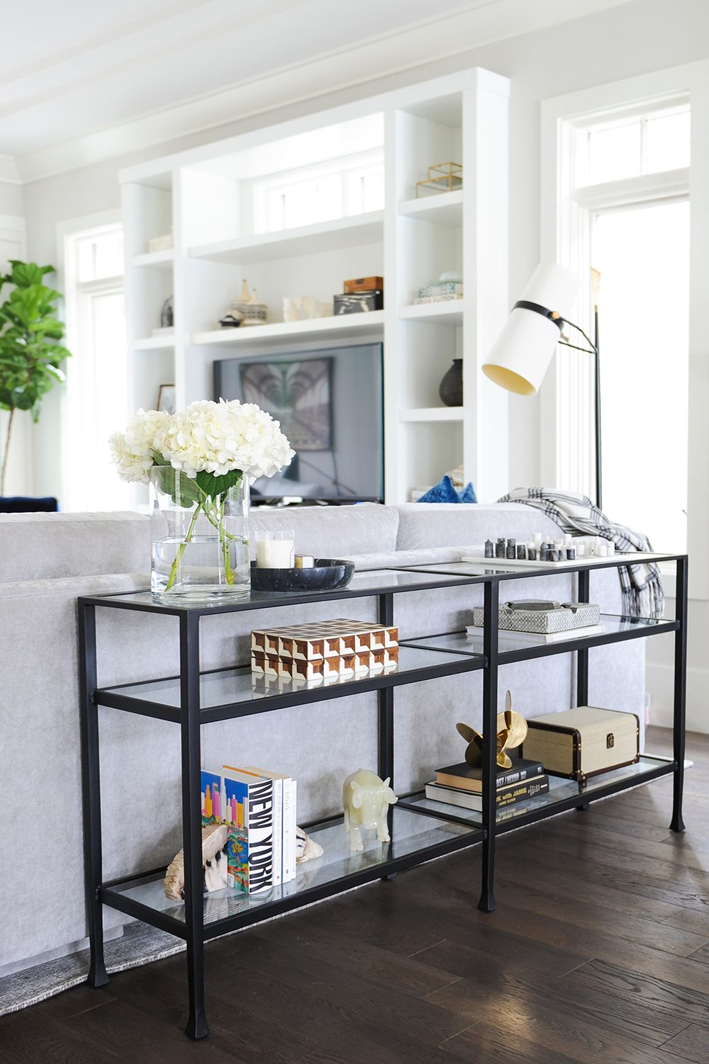 Simple black console table dressed up with artful accessories ...