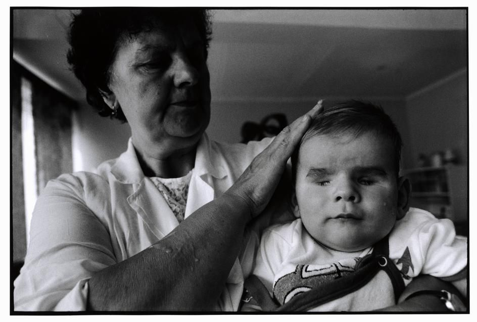 BELARUS. 1997. Chidlren's Home #1, Minsk. After feeding, an attendent soothes a boy born without eyes  Paul Fusco / Magnum Photos