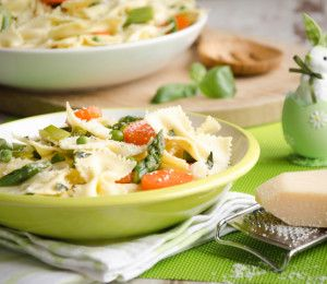Fresh bow-tie pasta served on a green plate with carrot,asparagus, onions, peas and parmesan with a bunny in egg for Easter
