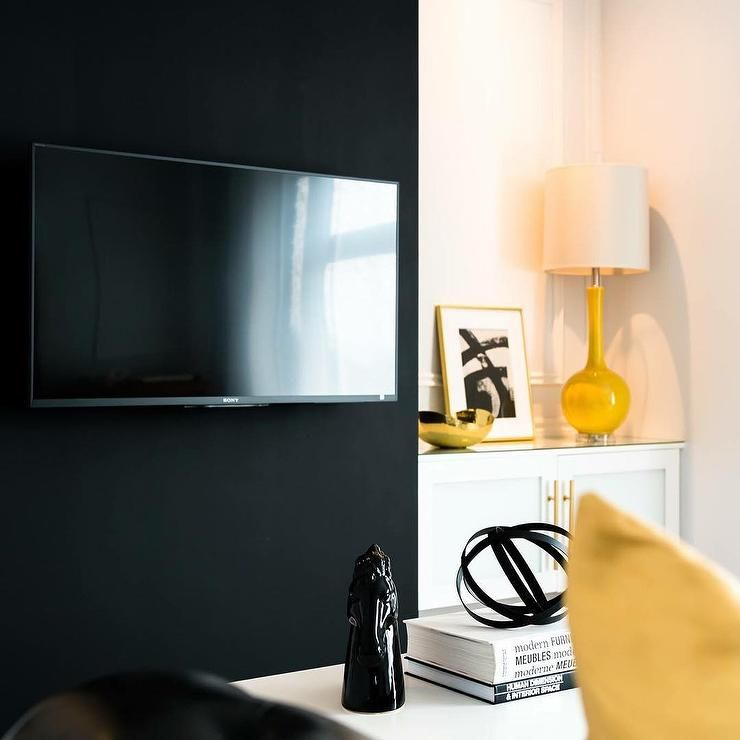Black And Yellow Living Room With A Black Accent Wall Lined With A Flatscreen Tv Next To A F Yellow Living Room Accent Walls In Living Room Yellow Accent Walls