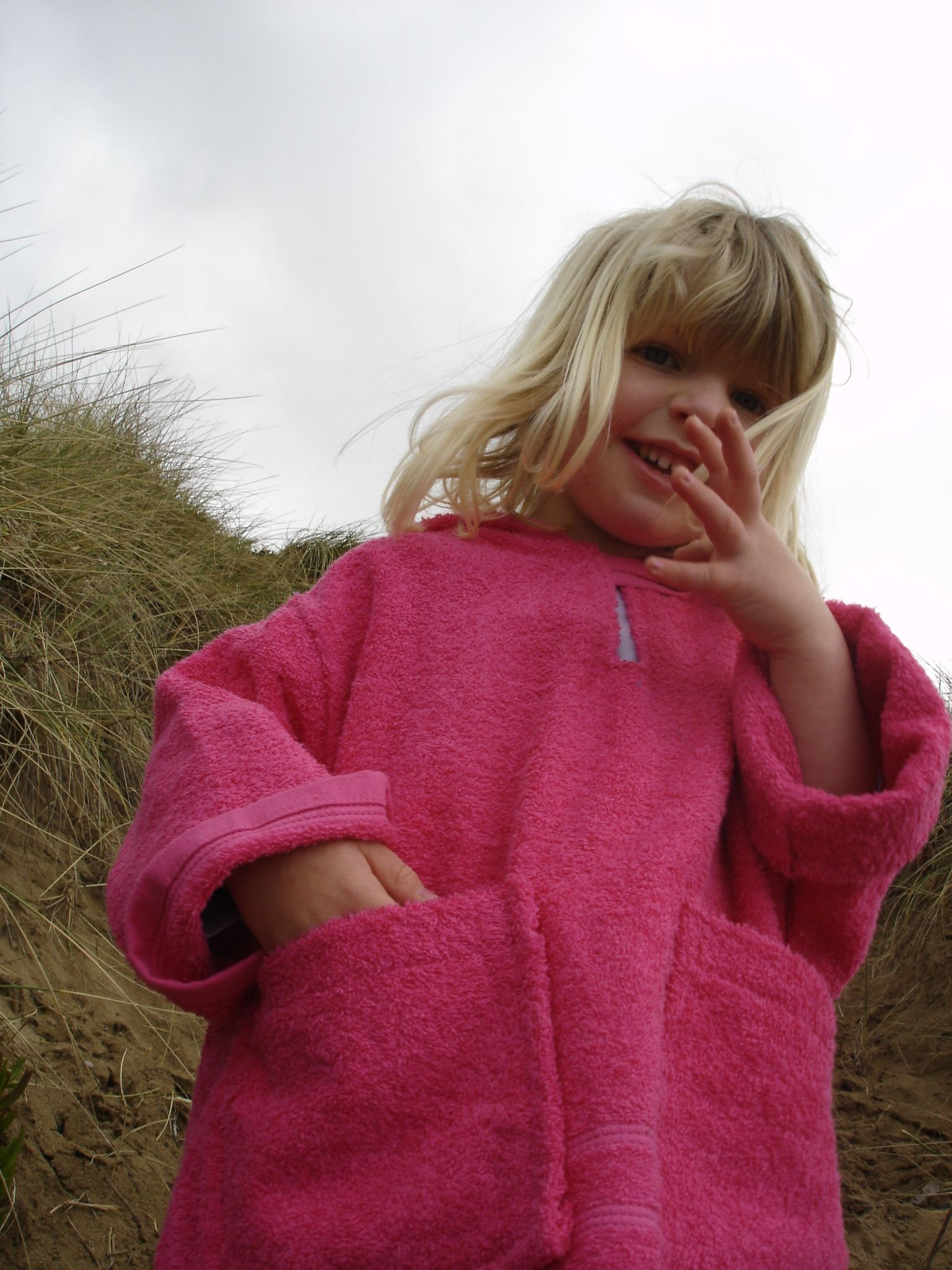 Bright pink towelling beach robe with two deep pockets and hood. Perfect for beach, swimming lessons, or cosying up after a bath.