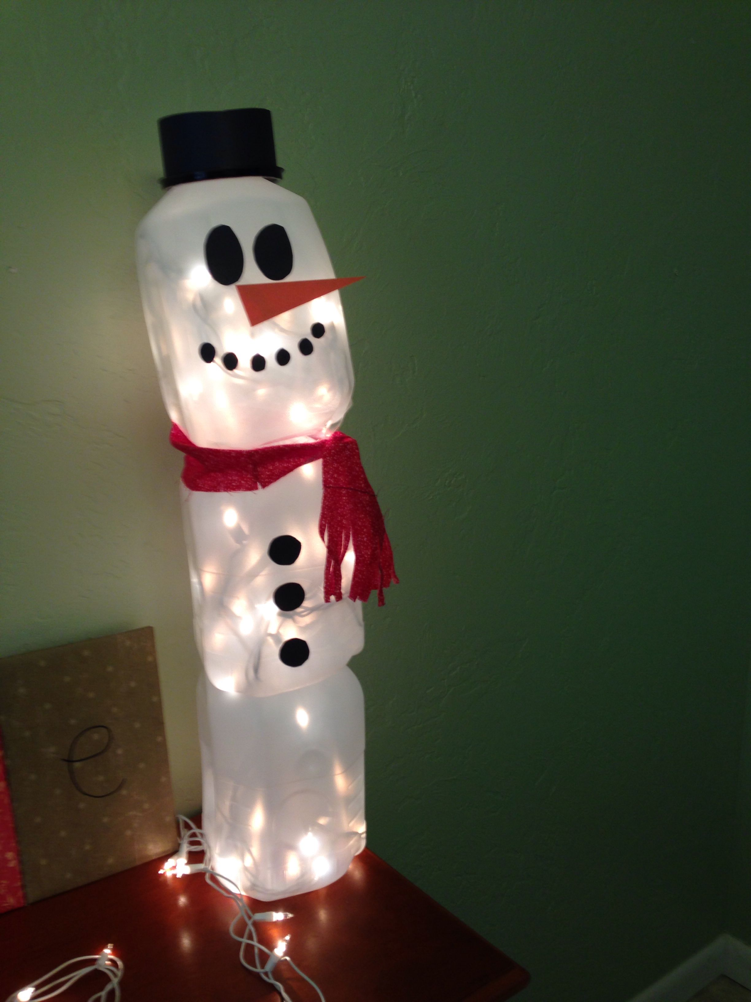 Milk jug snowman hat is made from a tupperware for Christmas crafts with milk jugs