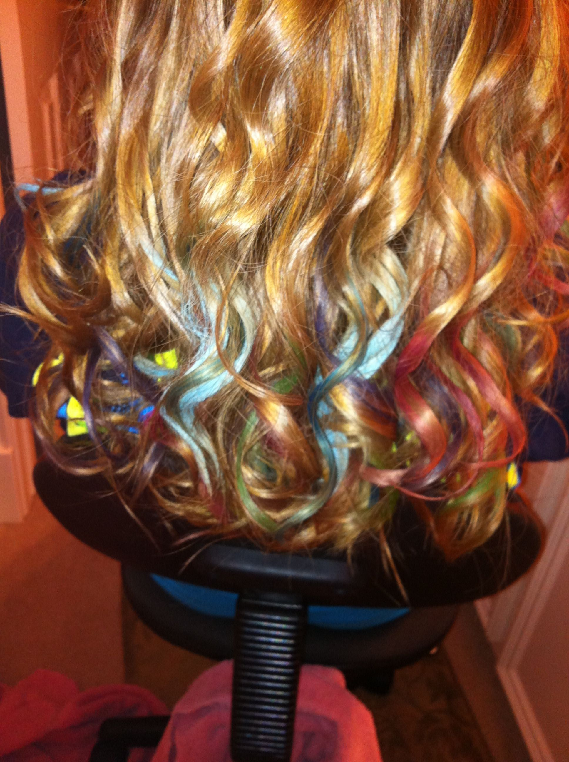 Hair chalking. It's actually done with oil pastels. Just rub the pastel crayon on a small, damp section of hair. Then hit it with the curling iron. This looks awesome!