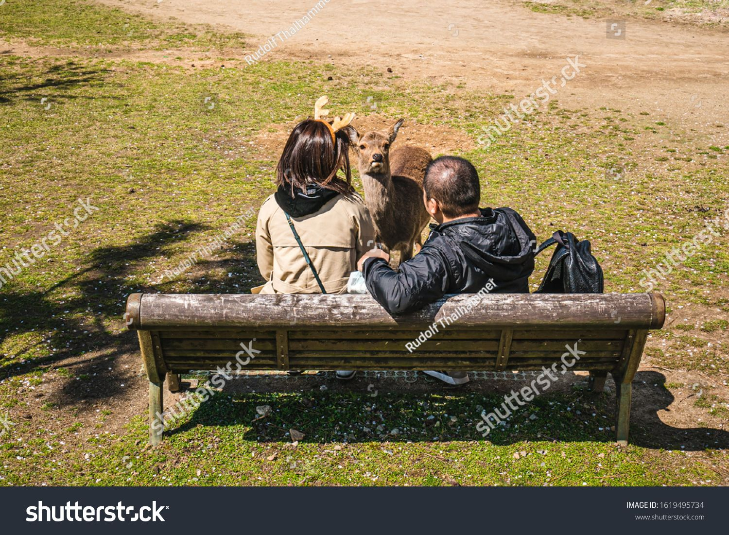 Two Tourist Sitting On A Park Bench Watching At A Deer In The Park Of Nara One Of Them Wearing A Headband In Form Of Dear A In 2020 Park Bench