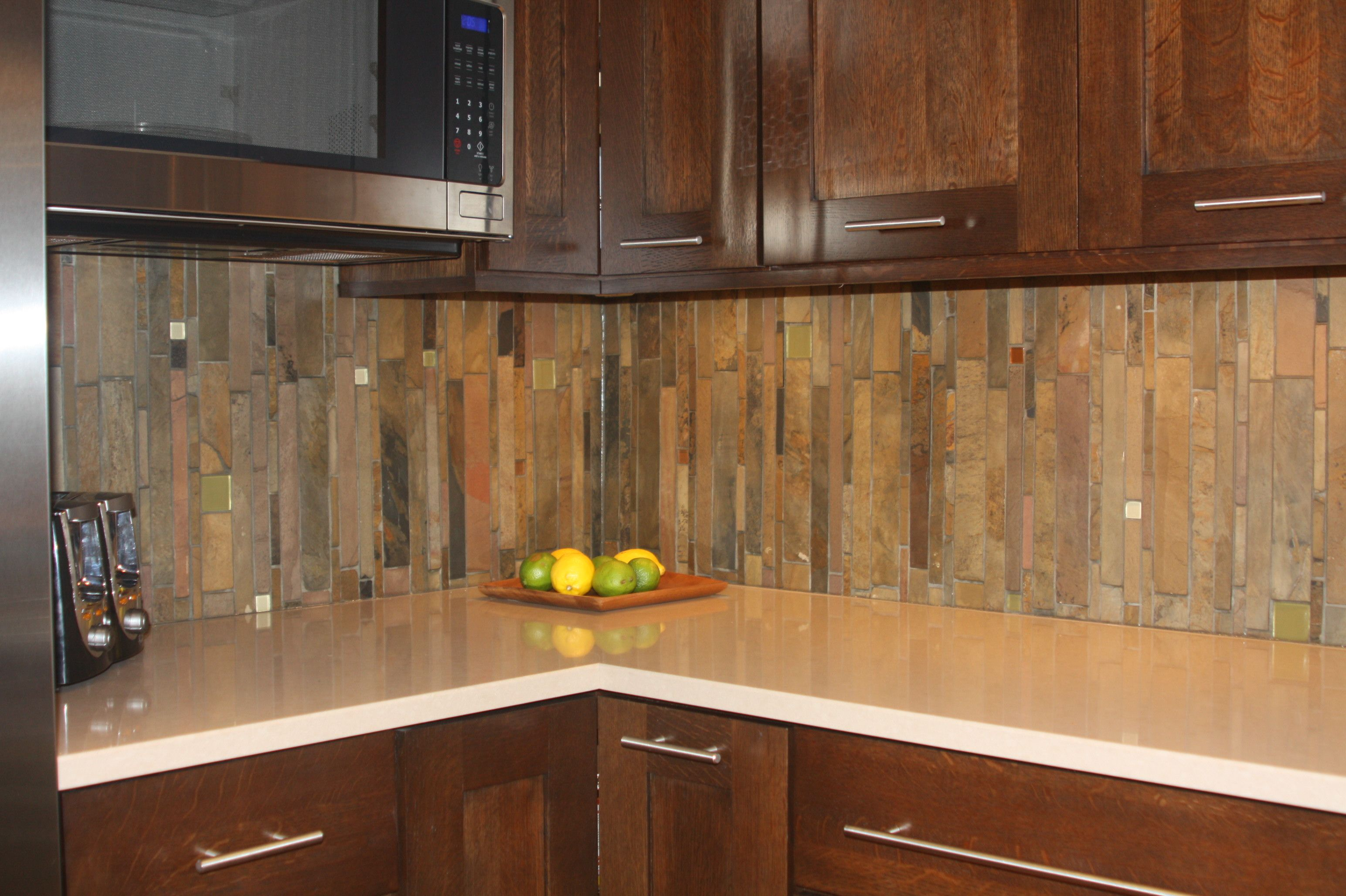 Vertical slate backsplash with a few glass tiles here and there