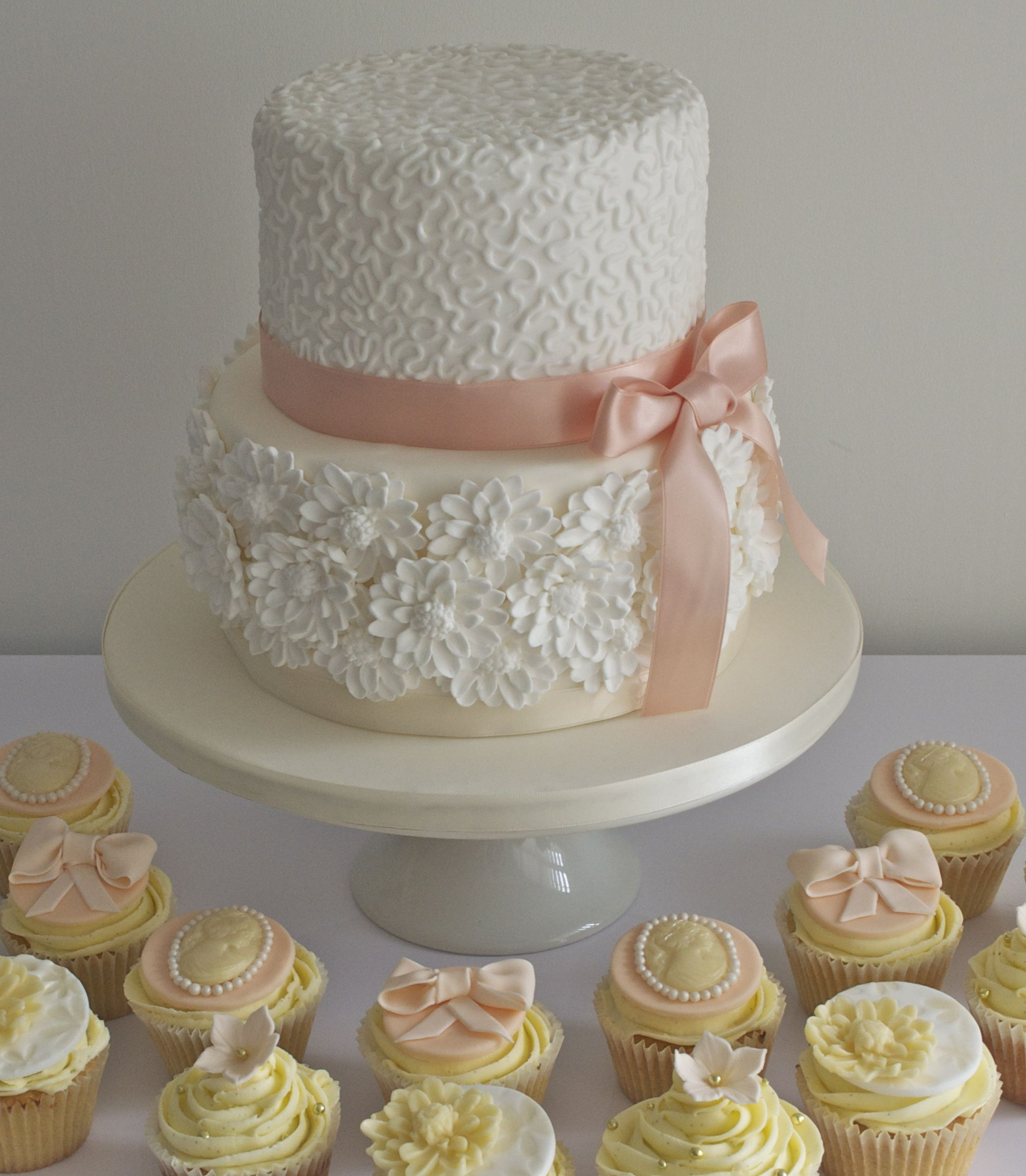 2 tier wedding cake on pedestal with cupcakes