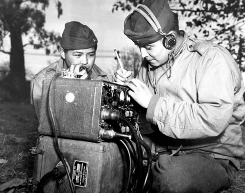 PFC Preseton Toledo and PFC Frank Toledo of the USMC were cousins attached to a Marine Artillery Regiment somewhere in the South Pacific as Navajo Code Talkers. They relayed orders over field radios using their native tongue, a code which the Japanese never broke throughout the duration of the war.