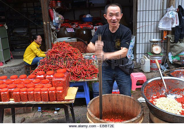 man copping red chilli at the down town food market in guiyang