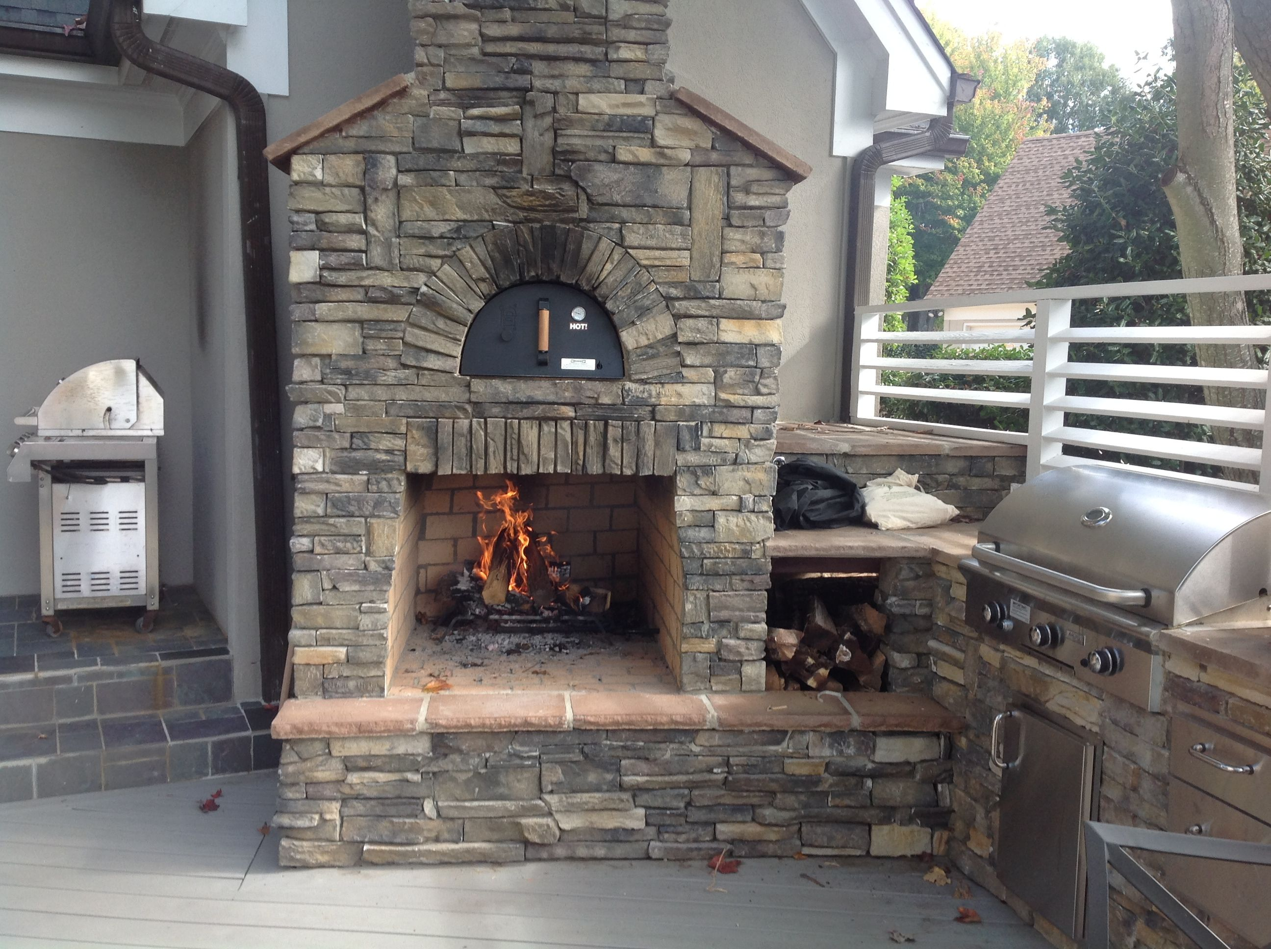 custom outdoor fireplace and pizza oven with an outdoor kitchen on