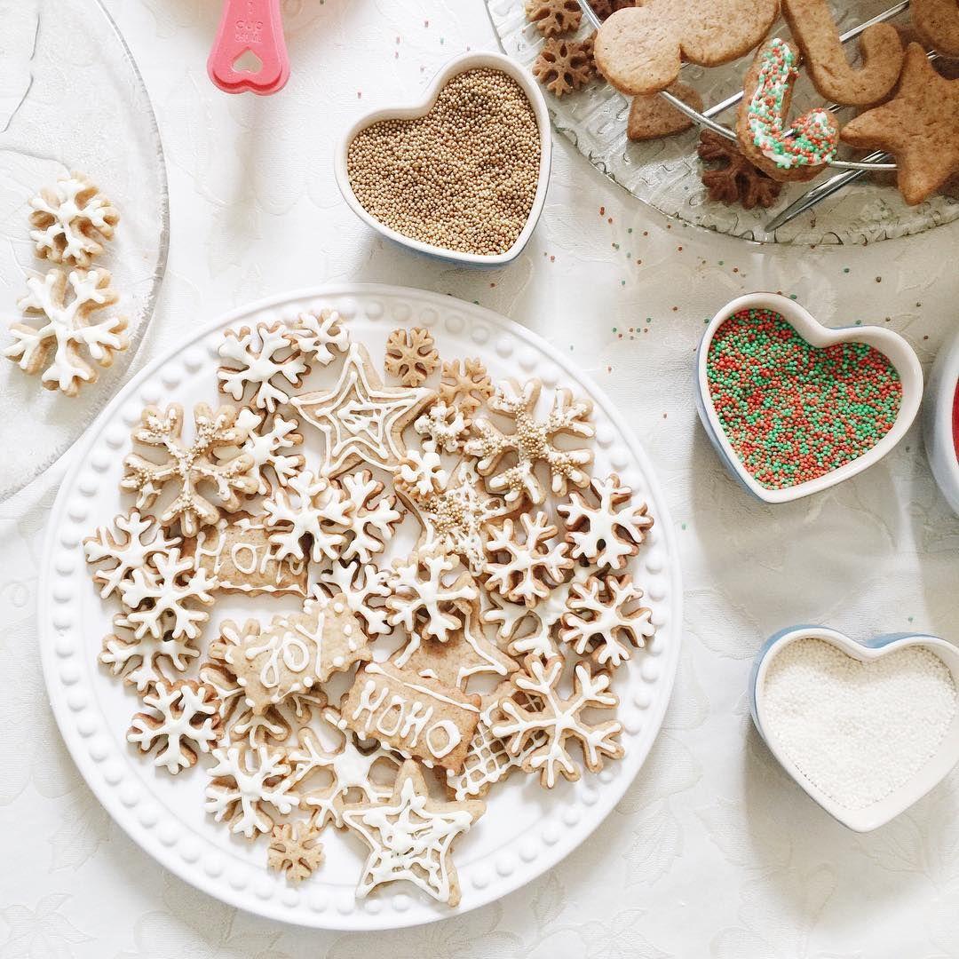 Foto clean de mesa com toalha branca e um prato cheio de biscoitos natalinos em forma de floquinhos de neve e potinhos com formato de coração com confeitos para decorar biscoitos.