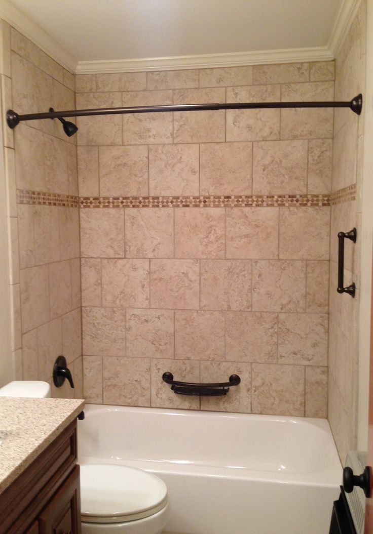 Beige tile bathtub surround with oil rubbed bronze fixtures - how to tile a tub surround