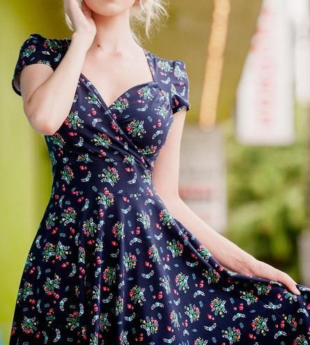 Wrapped and draped in soft, stretchy knit fabric, this cap sleeve dress might become a seasonal favorite. It's printed with bright cherry and light blue flowers on a navy background, and the dress wraps in a vintage-inspired style.